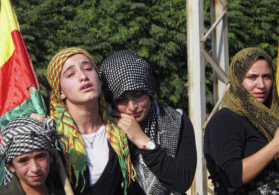Syrian Kurds mourn during the burial on August 27, 2013 of three Kurdish militia fighters from the Committees for the Protection of the Kurdish People (YPG) who were reportedly killed in an attack on their checkpoint by militants from the radical Islamist group Jabhat Al-Nusra in the Kurdish town of Derik, known in Arabic as al-Malikiyah, in Syria's northeastern Hasakeh governorate, on the border with Turkey and Iraq. More than 200,000 Syrians, predominantly Kurds, have escaped to Iraqi Kurdistan during the 29-months-long conflict in their homeland. Photo: AFP, AFP/Getty Images / 2013 AFP