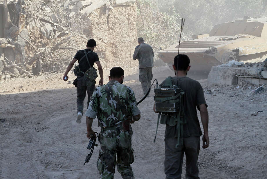 Syrian army soldiers are seen deployed in the Jobar neighborhood of Damascus on August 24, 2013. The president of Syria's main opposition group called on Western nations to intervene after a suspected chemical attack that left up to 1,300 dead in the country ravaged by civil war. Photo: STR, AFP/Getty Images / 2013 AFP
