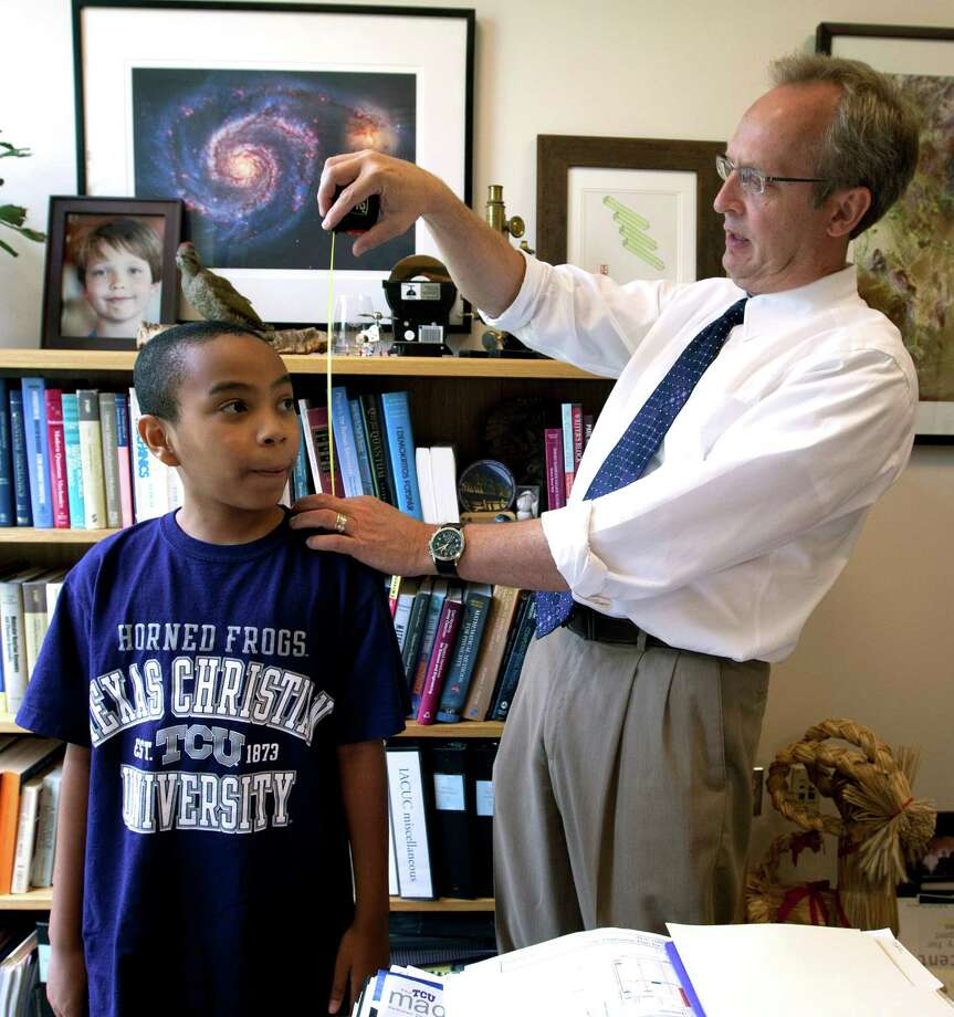 In this Tuesday, Aug. 27, 2013, photo, Carson Huey-You, 11, who is studying quantum physics at TCU, is measured by physics professor C. Magnus L. Rittbe in his office, in Fort Worth, Texas. He became TCU's youngest student ever when classes started last week. The physics major says he plans to be a quantum physicist. (AP Photo/The Fort Worth Star-Telegram, Joyce Marshall) Photo: Joyce Marshall, MBI / The Fort Worth Star-Telegram
