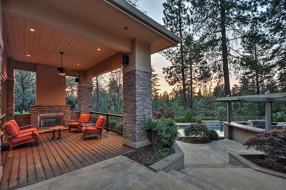 The home sits on a large wooded lot and offers views of the surrounding hillside.