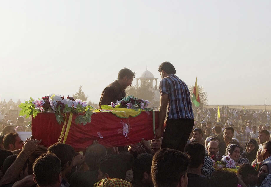 Syrian Kurds carry the coffin of a relative into a cemetery in the Kurdish town of Derik before the burial on August 27, 2013 of three Kurdish militia fighters from the Committees for the Protection of the Kurdish People (YPG) who were reportedly killed in an attack on their checkpoint by militants from the radical Islamist group Jabhat Al-Nusra south of the town, known in Arabic as al-Malikiyah, in Syria's northeastern Hasakeh governorate, on the border with Turkey and Iraq. A new wave of Syrians began pouring into northern Iraq in mid-August, seeking refuge from fighting between Kurdish forces and Islamist rebels, as well as from an economy in tatters. Syria's Kurds, who number over two million and are concentrated in the north and northeast of the country. Photo: AFP, AFP/Getty Images / 2013 AFP