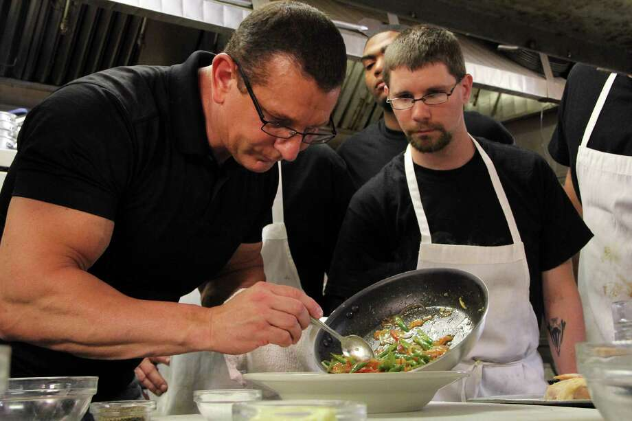 Cooks watch eagerly as Robert Irvine shows them how to make some new recipes, as seen on Food Network's Restaurant Impossible. Photo: Production Company