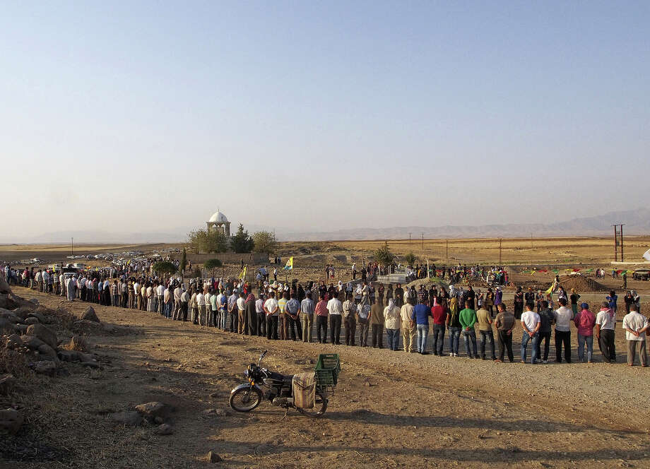 A crowd waits for the arrival of the bodies of three Kurdish fighters from the Committees for the Protection of the Kurdish People (YPG) for burial on August 27, 2013 in a cemetery in the Syrian-Kurdish town of Derik, following their killing in an attack on their checkpoint by militants from the radical Islamist group Jabhat Al-Nusra near the town, also known in Arabic as al-Malikiyah, in Syria's northeastern Hasakeh governorate, on the border with Turkey and Iraq. A new wave of Syrians began pouring into northern Iraq in mid-August, seeking refuge from fighting between Kurdish forces and Islamist rebels, as well as from an economy in tatters. Syria's Kurds, who number over two million and are concentrated in the north and northeast of the country. Photo: AFP, AFP/Getty Images / 2013 AFP
