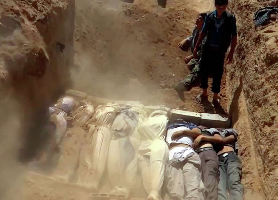 An image grab taken from a video uploaded on YouTube by the Local Committee of Arbeen on August 21, 2013 allegedly shows Syrians covering a mass grave containing bodies of victims that Syrian rebels claim were killed in a toxic gas attack by pro-government forces in eastern Ghouta and Zamalka, on the outskirts of Damascus. The allegation of chemical weapons being used in the heavily-populated areas came on the second day of a mission to Syria by UN inspectors, but the claim, which could not be independently verified, was vehemently denied by the Syrian authorities, who said it was intended to hinder the mission of UN chemical weapons inspectors. Photo: AFP, AFP/Getty Images / 2013 AFP