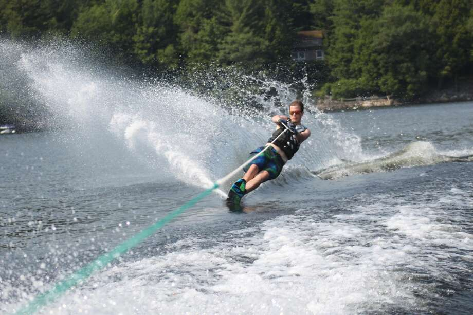 Zach Brunelle of Burnt Hills creates an arc of water as he skims along the Great Sacandaga Lake this summer with his new slalom ski in a photo taken by his father. (Dan Brunelle)