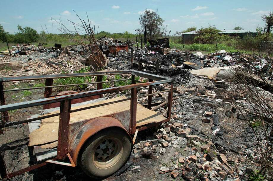 Only charred wood, ashes and scattered bricks are left from the Carrington family compound in rural Fort Bend County. Photo: Billy Smith II, Staff / Houston Chronicle