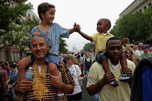 "John Mbugua and his son Giovanni Mbugua, 6, of San Jose, California, and Lavon Johnson and his son Mason Johnson, 2, of Fort Meade Maryland, greet one another while marching with  thousands of other people from Capitol Hill to the Lincoln Memorial during the 'Let Freedom Ring Commemoration and Call to Action' honoring the 50th anniversary of the historic March on Washington for Jobs and Freedom August 28, 2013 in Washington, DC. The 1963 landmark civil rights event was where Dr. Martin Luther King Jr. delivered his famous speech, saying, 'I still have a dream, a dream deeply rooted in the American dream...one day this nation will rise up and live up to its creed, ""We hold these truths to be self evident: that all men are created equal."" I have a dream . . .' Photo: Chip Somodevilla, Getty Images / 2013 Getty Images"