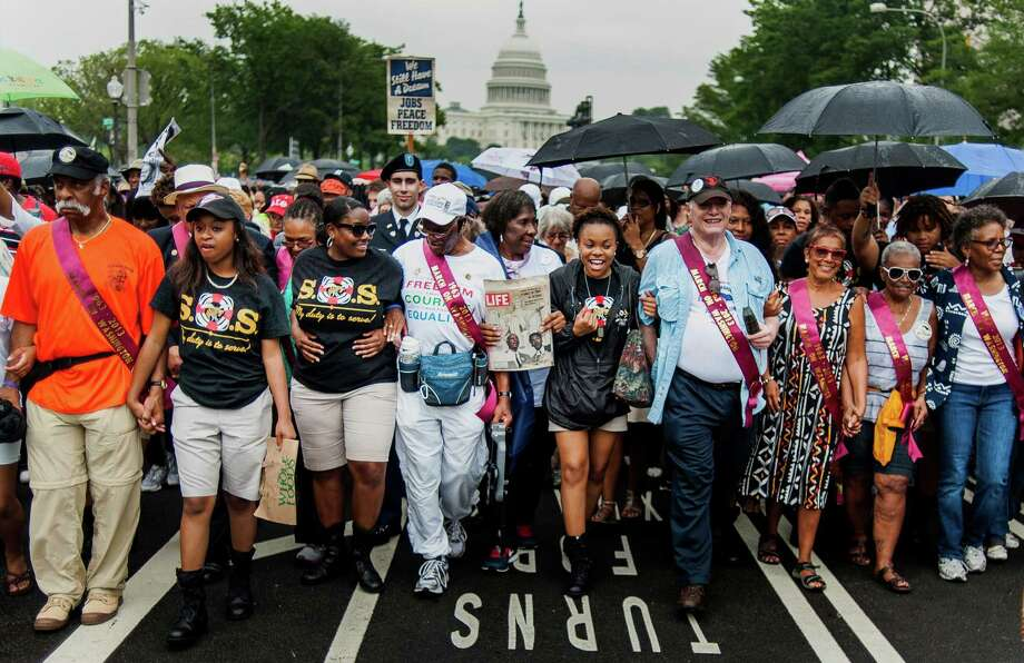 "Patricipants walk in the March for Jobs and Justice in Washington, D.C., U.S., on Wednesday, Aug. 28, 2013. The march is part of the Let Freedom Ring ceremony celebrating the 50th anniversary of the ""I have a Dream"" speech by Dr. Martin Luther King Jr. Photo: Pete Marovich, Bloomberg / © 2013 Bloomberg Finance LP"