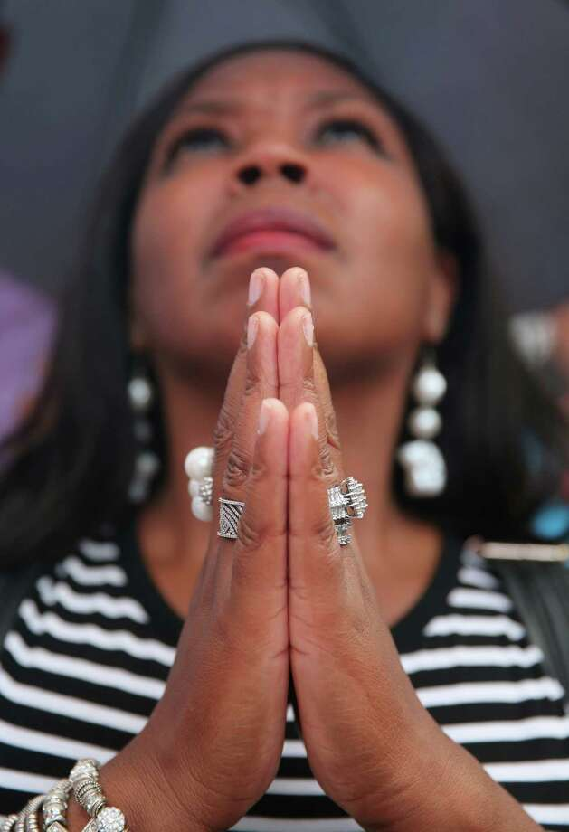 """Antoinette Thompson of Rochester, New York watches a giant screen in Times Square as U.S. President Barack Obama speaks on the 50th anniversary of Martin Luther King Jr.'s """"I Have a Dream"""" speech on August 28, 2013 in New York City. With the official ceremony in Washington D.C., a crowd gathered under a light rain in Manhattan's Times Square to commemorate the occasion. Photo: John Moore, Getty Images / 2013 Getty Images"""
