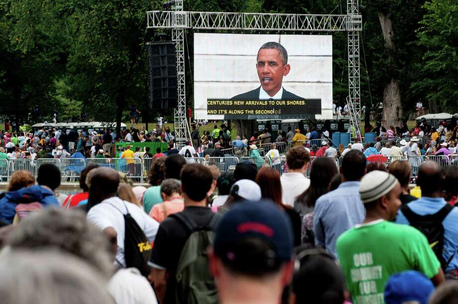 Participants listen to U.S. President Barack Obama's speech from the steps of the Lincoln Memorial on the National Mall in Washington, D.C., U.S., on Wednesday, Aug. 28, 2013. U.S. President Barack Obama, speaking from the same Washington stage where Martin Luther King Jr. delivered a defining speech of the civil rights movement, said that even as the nation has been transformed, work remains in countering growing economic disparities. Photo: Pete Marovich, Bloomberg / © 2013 Bloomberg Finance LP