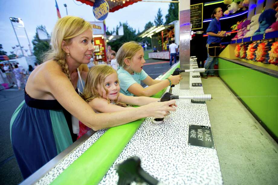 From left, Kelley Frey and her daughters, Grayson, left, and Gillian, right, play a water game at the St. Leo summer fair on Wednesday, August 28, 2013. The fair runs through Saturday, August 31, 2013. Photo: Lindsay Perry / Stamford Advocate