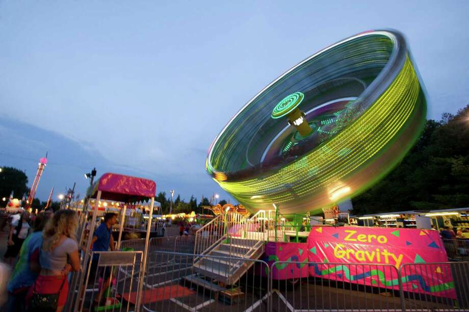 Rides whip through the air at the St. Leo summer fair on Wednesday, August 28, 2013. The fair runs through Saturday, August 31, 2013. Photo: Lindsay Perry / Stamford Advocate