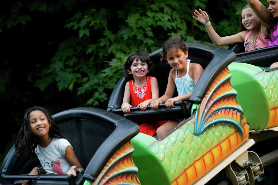 Chloe Trudeau, 6, left, and Izabel Fuhr, 7, right, ride in a dragon coaster at the St. Leo summer fair on Wednesday, August 28, 2013. The fair runs through Saturday, August 31, 2013. Photo: Lindsay Perry / Stamford Advocate