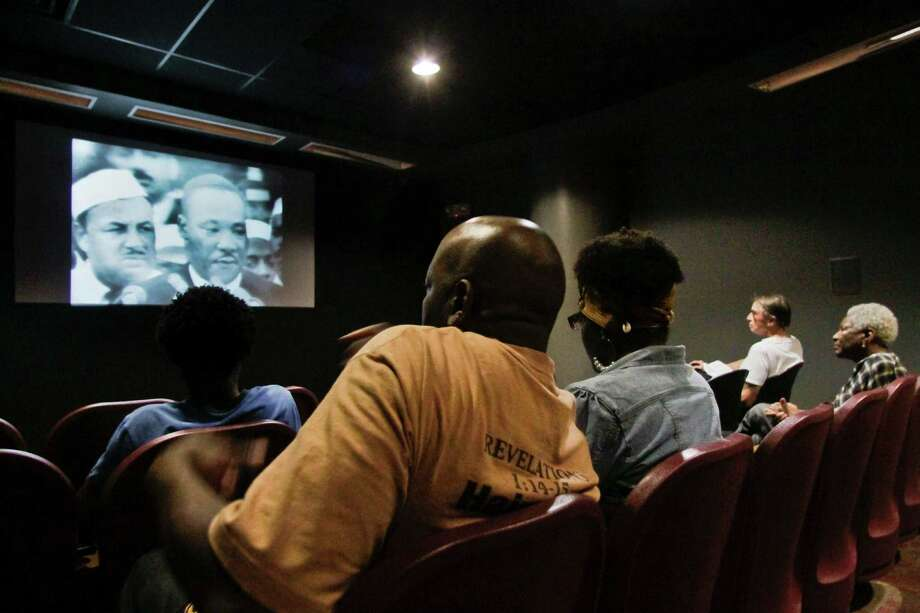 "Visitors to the African Burial Ground Monument view a video of Dr. Martin Luther King Jr., on Wednesday, Aug. 28, 2013 in New York.  Visitors screened Dr. Martin Luther King's ""I Have a Dream"" speech to commemorate the 50th anniversary of the March on Washington, where 250,000 people rallied decades ago for racial equality. Photo: Bebeto Matthews, Associated Press / AP"