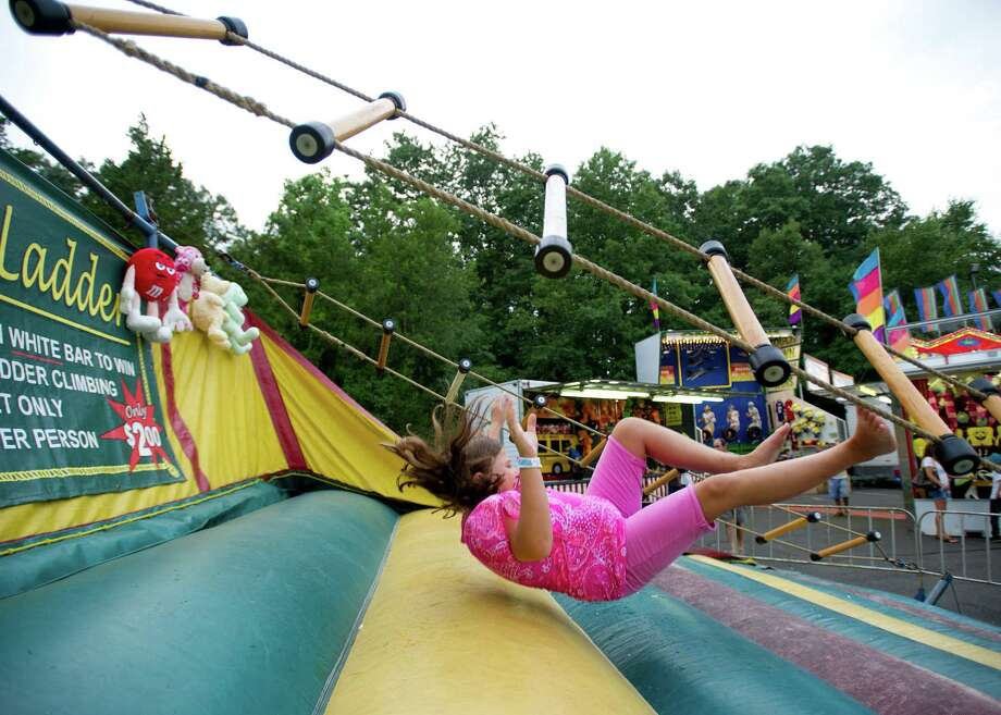Julia Cooney, 9, tries the Rope Ladder at the St. Leo summer fair on Wednesday, August 28, 2013. The fair runs through Saturday, August 31, 2013. Photo: Lindsay Perry / Stamford Advocate