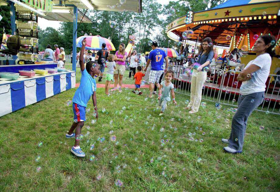 Kids play in a bunch of bubbles at the St. Leo summer fair on Wednesday, August 28, 2013. The fair runs through Saturday, August 31, 2013. Photo: Lindsay Perry / Stamford Advocate