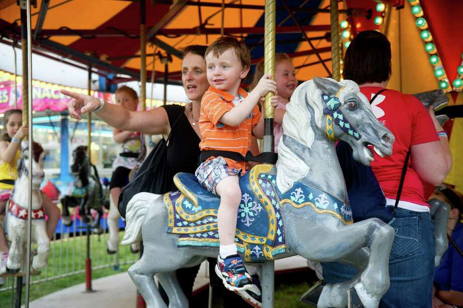 Jake McQuillan, 2, rides the carousel as his mother, Linda, stands beside him at the St. Leo summer fair on Wednesday, August 28, 2013. The fair runs through Saturday, August 31, 2013. Photo: Lindsay Perry / Stamford Advocate