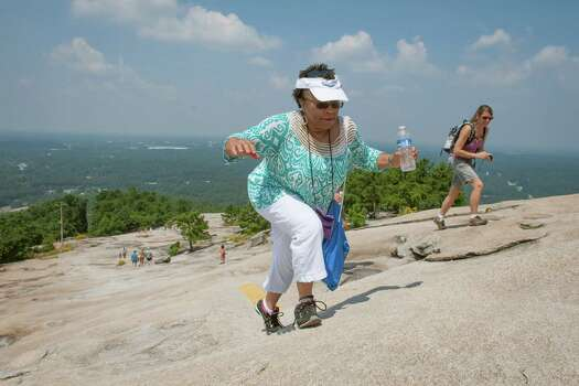 "Gail Scotton Baylor, 58, of High Point, N.C., climbs to the top of Stone Mountain for a ceremony celebrating the 50th anniversary of the Dr. Martin Luther King ""I have a dream"" speech, Wednesday, Aug. 28, 2013, in Stone Mountain, Ga. Photo: John Amis, Associated Press / FR69715 AP"