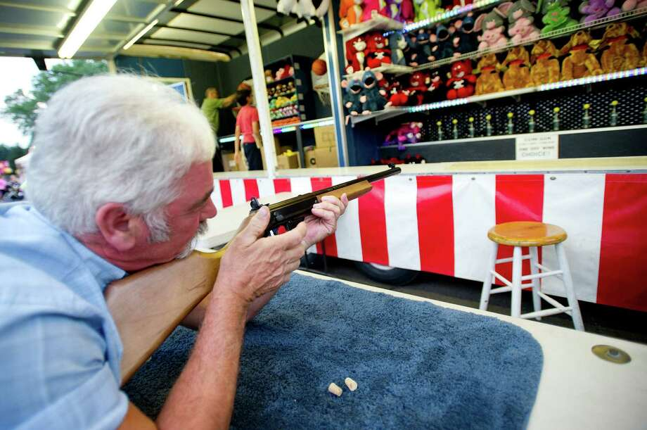 Frank Coppola uses a cork gun to try to knock a ball off a bottle at the St. Leo summer fair on Wednesday, August 28, 2013. The fair runs through Saturday, August 31, 2013. Photo: Lindsay Perry / Stamford Advocate