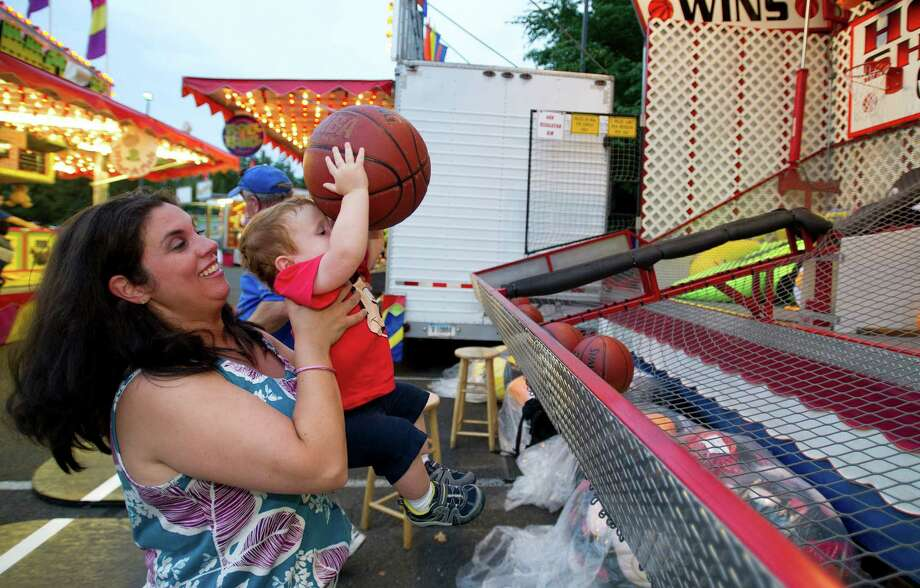 After watching his father try the game Hoop Shots, Matthew Kovatch, 1, got a lift from his mother, Tina, to give it a try himself at the St. Leo summer fair on Wednesday, August 28, 2013. The fair runs through Saturday, August 31, 2013. Photo: Lindsay Perry / Stamford Advocate