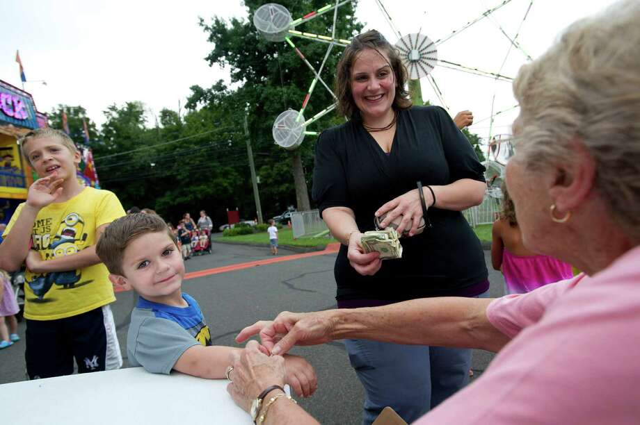 Dane Zagarino, 3, gets a bracelet as his mother, Theresa, pays for it at the St. Leo summer fair on Wednesday, August 28, 2013. The fair runs through Saturday, August 31, 2013. Photo: Lindsay Perry / Stamford Advocate