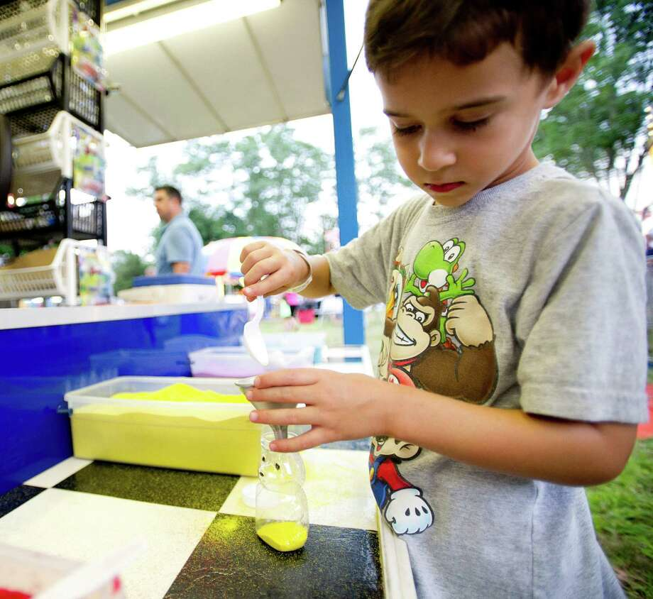 Harrison Munsch, 5, fills a bottle with colored sand at the St. Leo summer fair on Wednesday, August 28, 2013. The fair runs through Saturday, August 31, 2013. Photo: Lindsay Perry / Stamford Advocate
