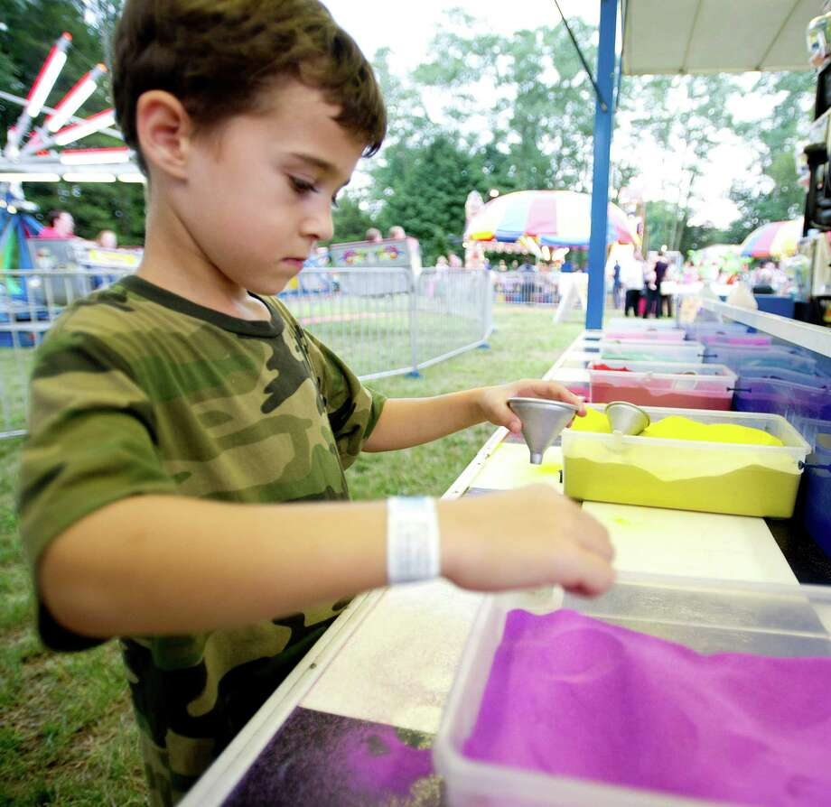 Ethan Munsch, 5, fills a bottle with colored sand at the St. Leo summer fair on Wednesday, August 28, 2013. The fair runs through Saturday, August 31, 2013. Photo: Lindsay Perry / Stamford Advocate