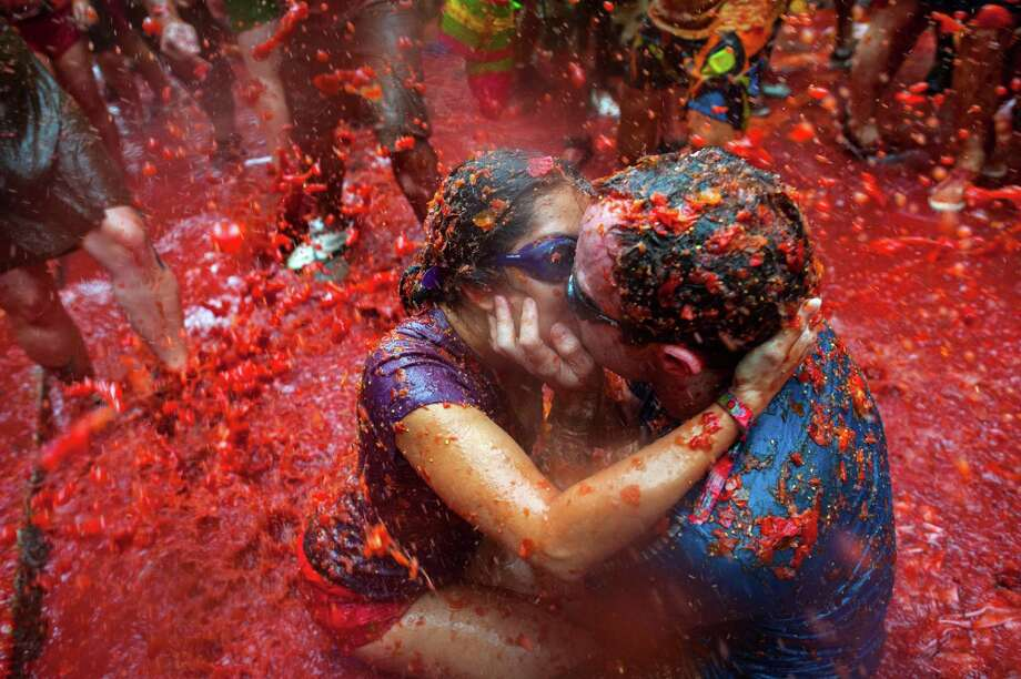 Two Revellers kiss each other covered in tomato pulp while participating the annual Tomatina festival on August 28, 2013 in Bunol, Spain. An estimated 20,000 people threw 130 tons of ripe tomatoes in the world's biggest tomato fight held annually in this Spanish Mediterranean town. Photo: David Ramos, Getty Images / 2013 Getty Images