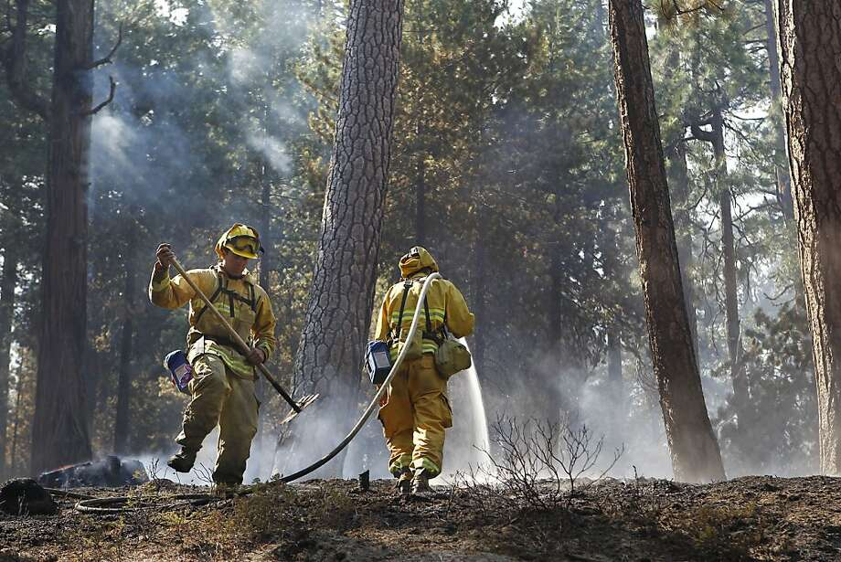 Firefighters Trever Winters (left) and Leno Estrada put out hot spots along Highway 120 near Groveland. Photo: Michael Macor, San Francisco Chronicle