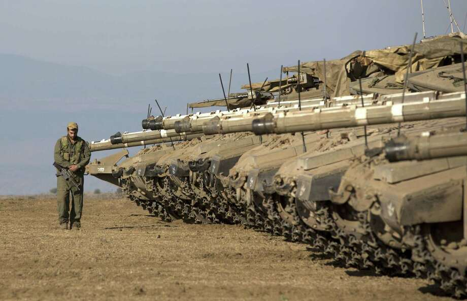 "An Israeli soldier walks next to tanks stationed in the Israeli-annexed Golan Heights near the border with Syria on Wednesday. Israel will strike back ""fiercely"" if Syria attacks the Jewish state, Prime Minister Benjamin Netanyahu said. Photo: MENAHEM KAHANA, Staff / AFP"