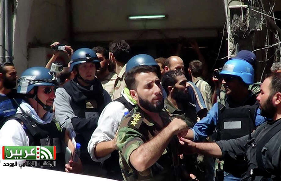 In this citizen journalism image provided by the United media office of Arbeen which has been authenticated based on its contents and other AP reporting, UN investigation team with blue helmets, walk with Syrian rebels in Damascus countryside of Zamalka, Syria, Wednesday, Aug. 28, 2013. U.N. chemical weapons experts headed to a Damascus suburb on Wednesday for a new tour of areas struck by a purported poison gas attack, activists said, as Western powers laid the groundwork for a possible punitive strike and the U.N. chief pleaded for more time for diplomacy. (AP Photo/United media office of Arbeen) Photo: HOEP / United media office of Arbeen