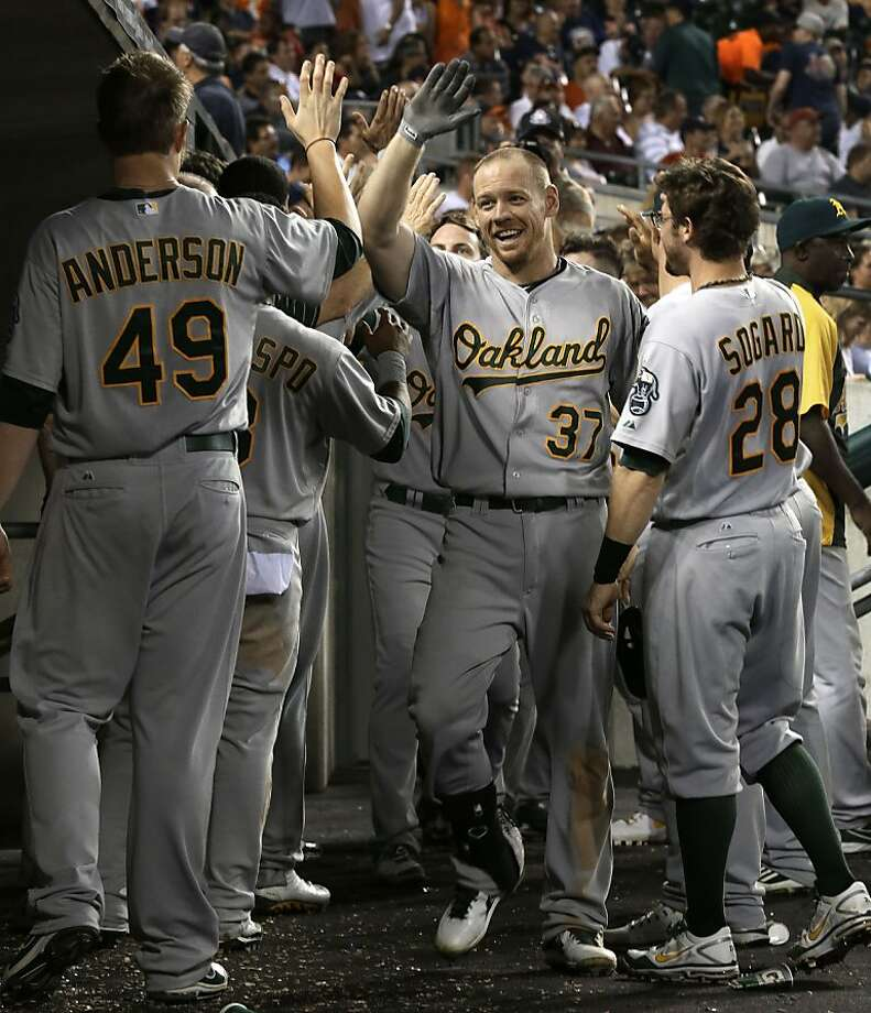 Brandon Moss is at the center of a happy dugout after his a three-run homer in the eighth inning. Photo: Paul Sancya, Associated Press