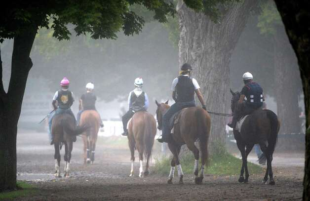 Fog shrouds the main track as horses go out for their morning work Wednesday morning, Aug 28, 2013, at Saratoga Race Course in Saratoga Springs, N.Y.  (Skip Dickstein/Times Union) Photo: SKIP DICKSTEIN