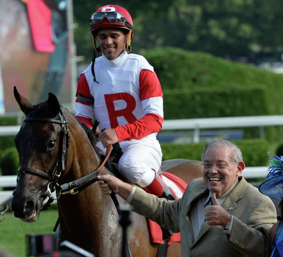 Owner Ken Ramsey give the thumbs-up sign as he leads Granny Mc's Kitten to the winner's circle after winning the 9th running of The P. G. Johnson stake Aug. 28, 2013 at the Saratoga Race Course Aug 28, 2013 in Saratoga Springs, N.Y.  Ramsey is now the winningest owner in the history of Saratoga Race Course.  (Skip Dickstein/Times Union) Photo: SKIP DICKSTEIN