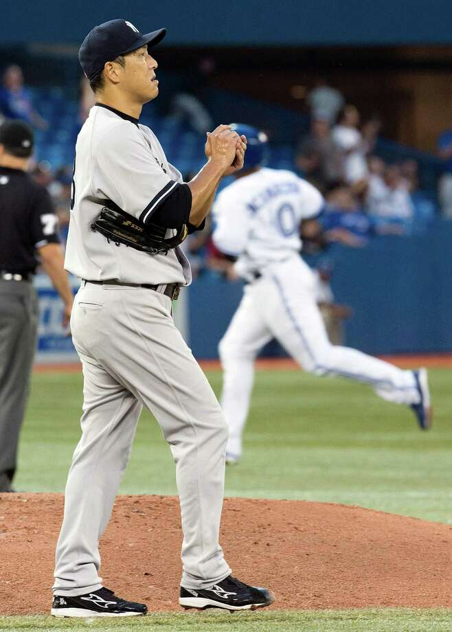 Toronto Blue Jays' Edwin Encarnacion rounds the bases after hitting a two-run home run as New York Yankees starting pitcher Hiroki Kuroda, of Japan, rubs up a new ball during the second inning of a base ball game in Toronto on Wednesday, Aug. 28, 2013. (AP Photo/The Canadian Press, Frank Gunn) ORG XMIT: FNG106 Photo: Frank Gunn / CP