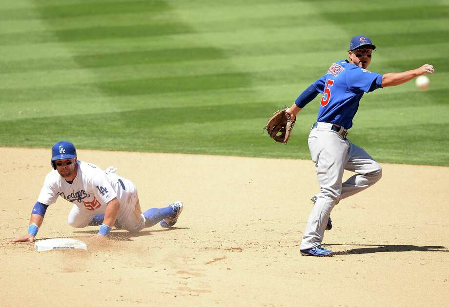 The Dodgers' Skip Schumaker, left, breaks up a double play, something Yasiel Puig, who was replaced by Schumaker, failed to attempt earlier in the game. Photo: Harry How, Staff / 2013 Getty Images
