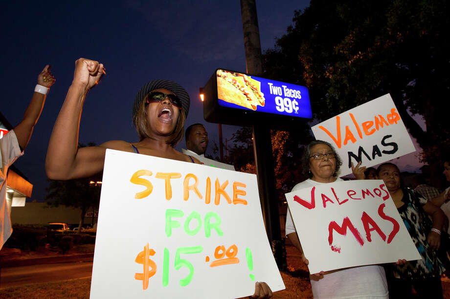 LaToya White, left, and Austraberta Rodriguez, right, stand outside Jack In the Box in protest of wages paid to fast food employees, Thursday, Aug. 29, 2013, in Houston. Protestors joined the national movement to try and increase wages to $15 per hour for minimum wage. Photo: Cody Duty, Houston Chronicle / © 2013 Houston Chronicle