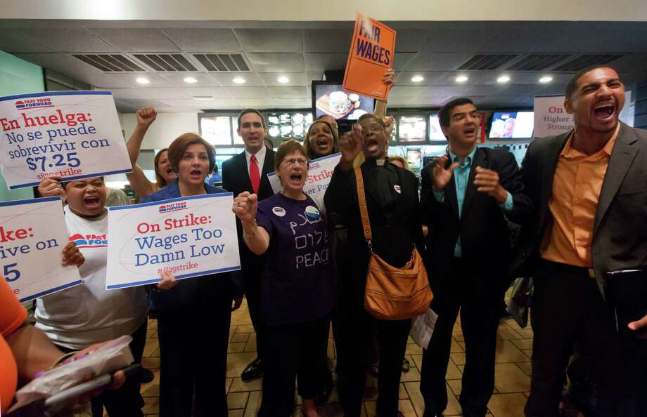 Protesting fast food workers, joined by New York City Council Speaker and mayoral candidate Christine Quinn, second left, and protest organizers, chant inside a McDonald's restaurant on New York's Fifth Avenue,  Thursday Organizers say thousands of fast-food workers are set to stage walkouts in dozens of cities around the country Thursday, part of a push to get chains such as McDonald's, Taco Bell and Wendy's to pay workers higher wages. (AP Photo/Richard Drew) Photo: Associated Press
