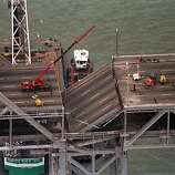 In this Oct. 21, 1989 file photo, a crane mounted on a barge, is towed into position, ready to lift a section of the collapsed San Francisco-Oakland Bay Bridge in San Francisco, Calif., on Oct. 21, 1989.  Crowded roadways and packed buses, trains and ferries are on tap for commuters starting Wednesday night, Aug. 28, 2013 when officials shut down the San Francisco-Oakland Bay Bridge to traffic in preparation for a new $6.4 billion span opening late Monday, Sept. 2 or early Tuesday.