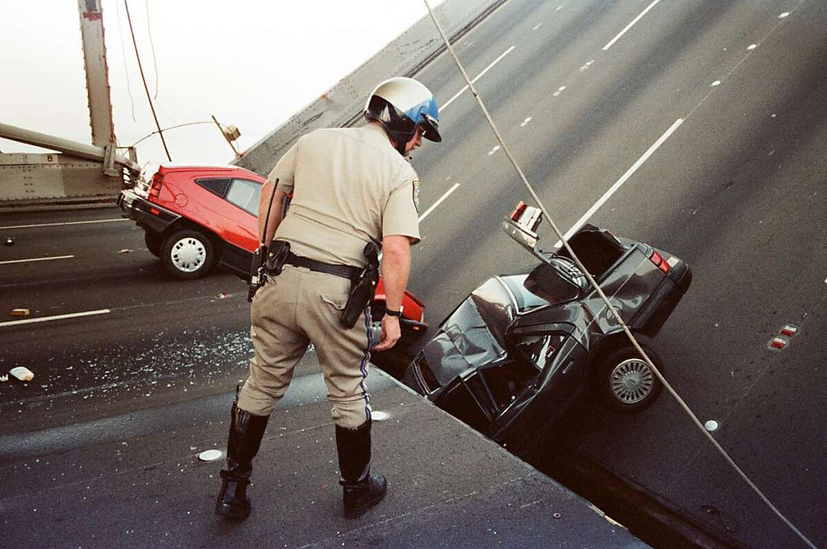 A California Highway Patrol officer checks the damage to cars that fell when the upper deck of the Bay Bridge collapsed onto the lower deck after the Loma Prieta earthquake in San Francisco. (Oct. 17, 1989.)