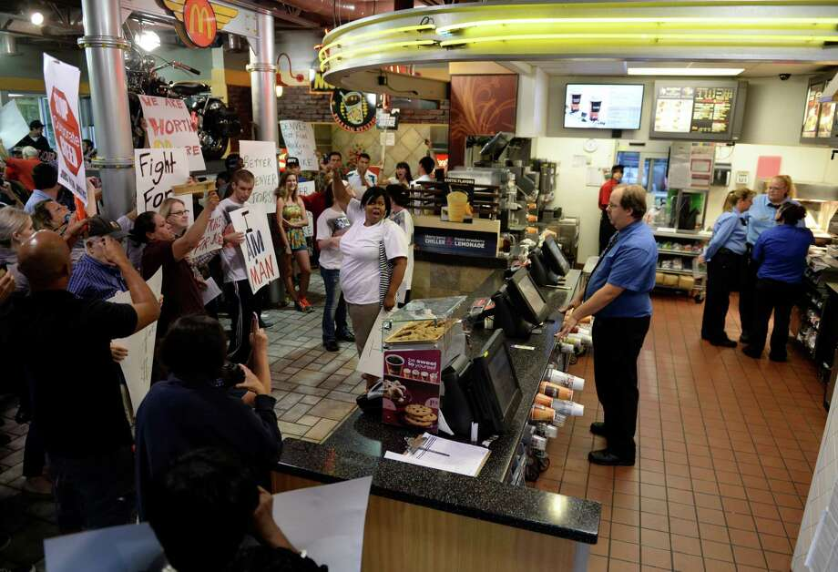 Protesters, asking for better wages for fast food workers, take over a McDonald's in Northglenn, Colo., on Thursday. They are asking for $15 an hour for workers in this nationally organized event. Photo: RJ Sangosti, Getty / Copyright - 2013 The Denver Post, MediaNews Group.