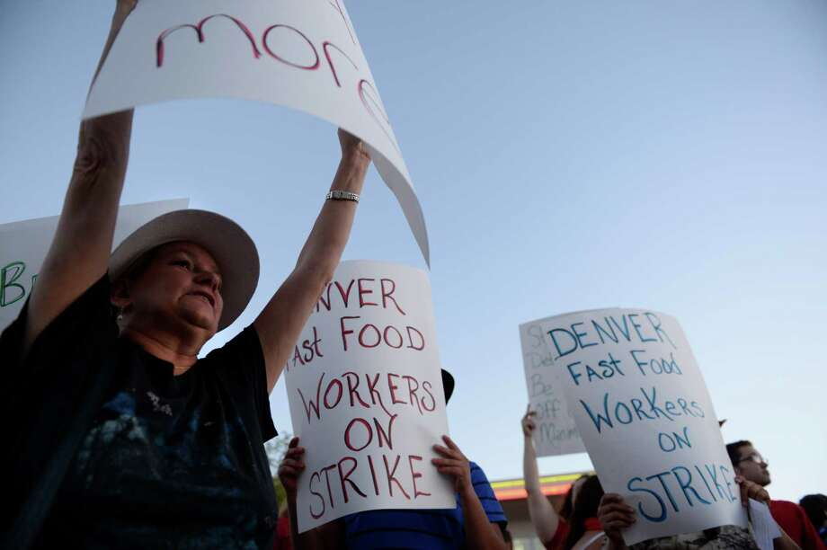 : Mary Glenn, left, joined other protesters asking for better wages for fast food workers stand outside a McDonald's in Northglenn, Colo. on Thursday. The asking rate is $15 an hour for workers in this nationally organized event. Photo: RJ Sangosti, Getty / Copyright - 2013 The Denver Post, MediaNews Group.