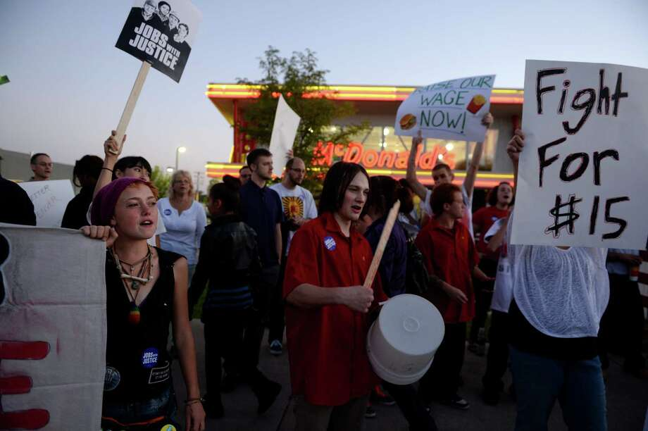 Protesters asking for better wages for fast food workers stand outside a McDonald's in Northglenn, Colo., on Thursday. The asking rate is $15 an hour for workers in this nationally organized event. Photo: RJ Sangosti, Getty / Copyright - 2013 The Denver Post, MediaNews Group.