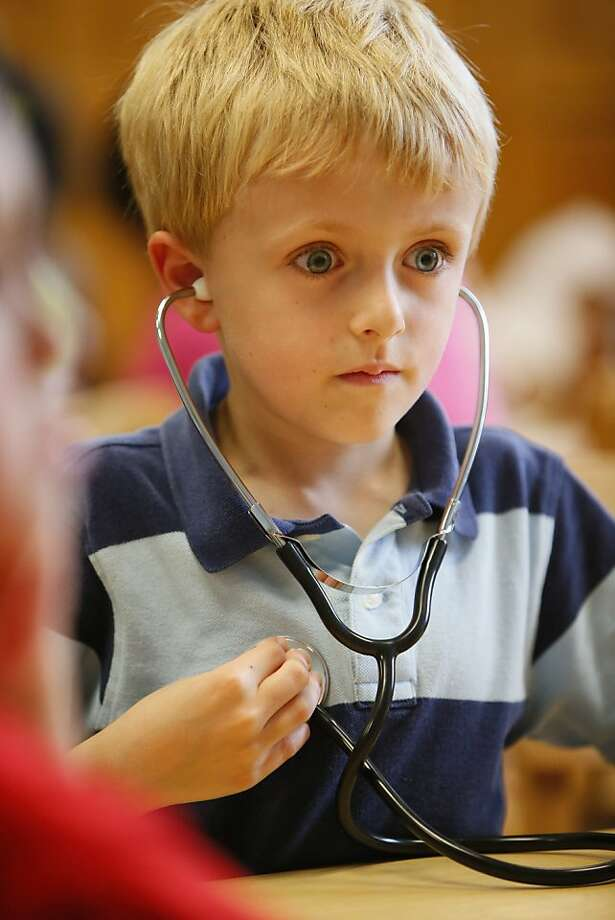 "Ticker shock:Seven-year-old Owen Rung of East Aurora, N.Y., seems awed by the sound of his heartbeat at the ""All About Me"" summer discovery camp at the Buffalo Museum of Science. Photo: Derek Gee, Associated Press"