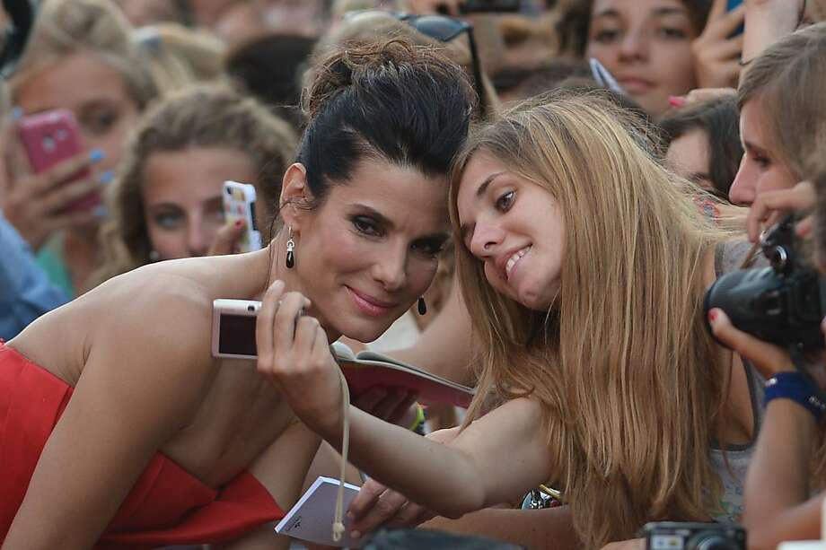 A shot that will never be deleted: Sandra Bullock poses with a fan for a cell phone photo before the opening ceremony of the 70th 