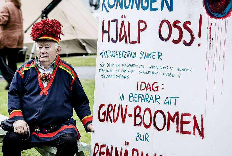 Sami man Josef Pittja holds a sign appealing to Swedish King Carl Gustaf for help in blocking an open pit mine planned by a British company on land used by the Sami for reindeer herds. Photo: Carl-Johan Utsi, Associated Press