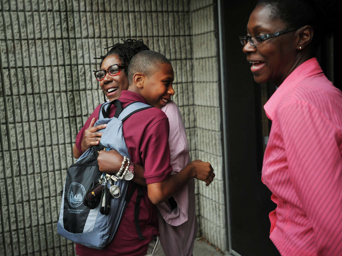 Resource room teacher Melodie Thigpen, left, welcomes back a returning student as she and academic assistant Ann-Marie Griffith, right, welcome back students on the first day of school at the reopened Dunbar School on Union Avenue in Bridgeport, Conn. on Thursday, August 29, 2013.