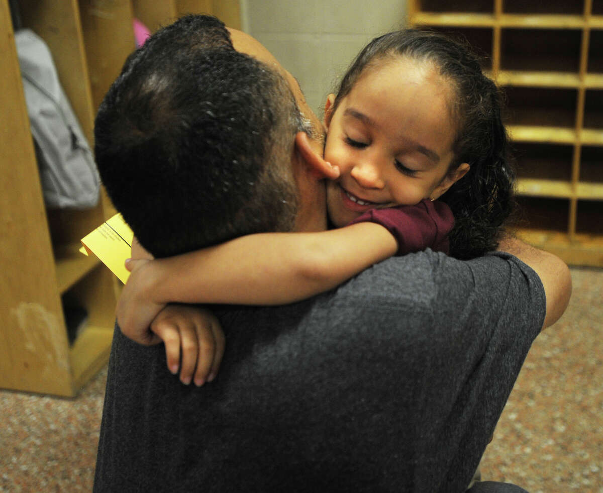 Liana Estrada, 4, hugs her father Luis goodbye on her first day of kindergarten at the reopened Dunbar School on Union Avenue in Bridgeport, Conn. on Thursday, August 29, 2013.
