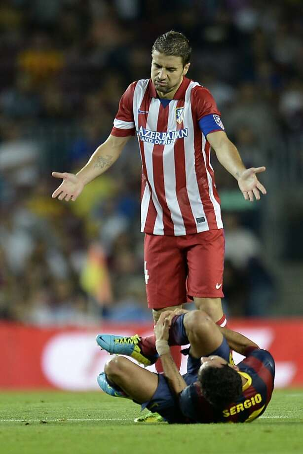 Atletico Madrid's Gabi (standing) and Barcelona's Sergio Busquets tangle during Wednesday's Spanish Super Cup. Photo: Lluis Gene, AFP/Getty Images