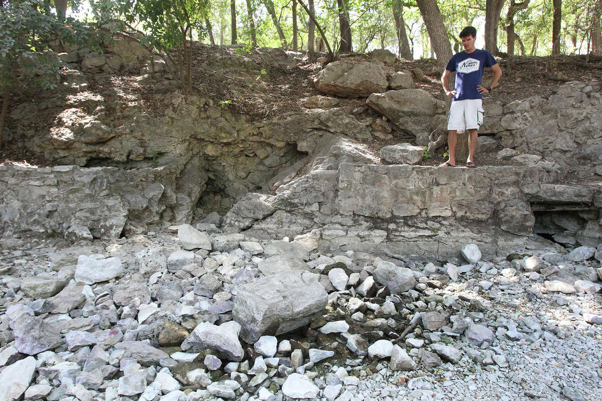 Clarke Raines, vacationing from Austin, checks the spring flow area and sees no water for the first time in his experience. The water channel below one of the main outlets at Comal Springs is dry as water levels at Canyon Lake and the Guadalupe and Comal rivers flow at seasonal levels on August 8, 2014.